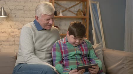 nicely : Grandfather and grandson sitting on the couch using tablet and looking at the camera. Home comfort, family idyll, cosiness concept. 60 fps Stock Footage