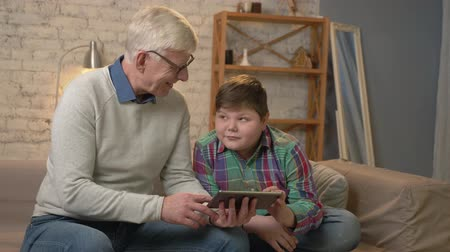nicely : Grandfather and grandson sitting on the couch using a tablet looking at each other, smiling. Home comfort, family idyll, cosiness concept. 60 fps Stock Footage