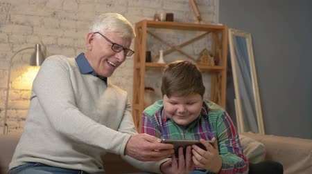 cosiness : Grandfather and grandson sitting on the couch using a tablet watching a funny movie, laughing, smiling. Home comfort, family idyll, cosiness concept 60 fps