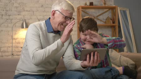 nicely : Grandfather and grandson are sitting on the sofa using a tablet, waving their hand in the video chat, greeting, smiling and laughing. Home comfort, family idyll, cosiness, internet, video concept. 60 fps