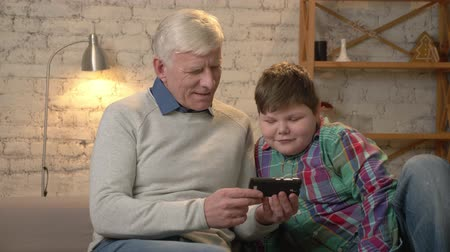 nicely : Grandfather and grandson sitting on the couch using a smartphone watching interesting videos, interested, serious faces. Home comfort, family idyll, cosiness concept. 60 fps Stock Footage
