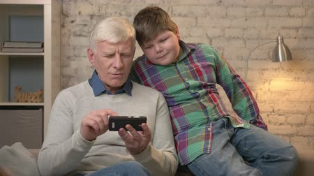 prarodič : Grandfather and grandson are sitting on the couch using a smartphone, playing on a smartphone. Young fat boy and grandfather. Home comfort, family idyll, cosiness concept. 60 fps