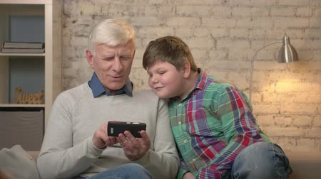 teen age : Grandfather and grandson are sitting on the couch using a smartphone, playing on a smartphone. Young fat boy and grandfather. Home comfort, family idyll, cosiness concept 60 fps