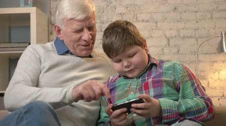 dede : Grandfather and grandson sitting on the sofa using a smartphone, speaking, a fat child is playing on a smartphone. Young fat boy and grandfather. Home comfort, dialog, family idyll, cosiness concept. 60 fps