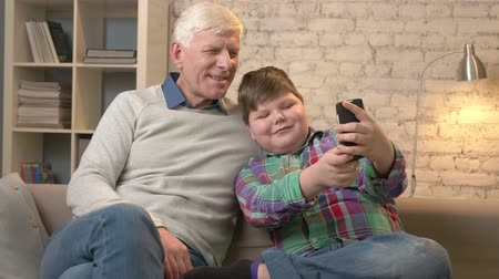 nicely : Grandfather and grandson are sitting on the sofa using a smartphone, do selfie. Young fat child and grandfather smiling. Home comfort, family idyll, cosiness concept. 60 fps Stock Footage
