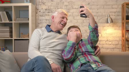 nicely : Grandfather and grandson are sitting on the sofa using a smartphone, making selfie. Rejoice in victory, laugh, they are happy. Young fat child and grandfather. 60 fps Stock Footage