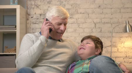nicely : Grandfather and grandson are sitting on the couch. The old man holds a smartphone in his hand, talks on the phone, gives the phone to his grandson. Home comfort, dialog, family idyll, cosiness concept. 60 fps Stock Footage
