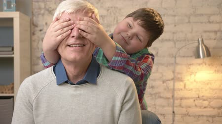 dede : Young fat child closes his grandfathers eyes with his hands. Guess who. A game, prank. Grandson looks into the camera and makes funny faces. Happy family concept 60 fps Stok Video