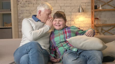 nicely : Grandfather whispers in the ear of his grandson a funny secret, gossip. Young fat boy laughing. Home comfort, family idyll, cosiness concept. 60 fps