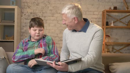 nicely : Elderly man is teaching a young fat guy. Grandfather and grandson, happy family, home cosiness concept. 60 fps