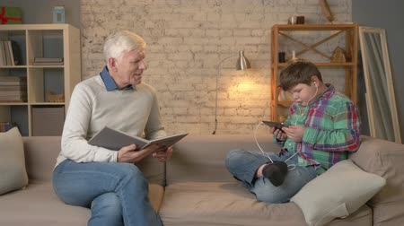 nicely : The difference of generations. Elderly man is sitting on the couch and reading a book, a young fat guy uses a tablet and headphones. Home comfort, family idyll, cosiness concept. 60 fps