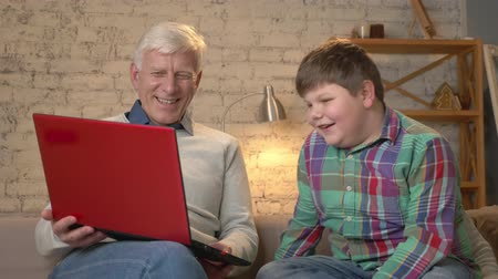 teen age : Grandfather and grandson are sitting on the couch and watching a funny movie on the laptop, laughing. Home comfort, family idyll, cosiness concept, difference of generations 60 fps