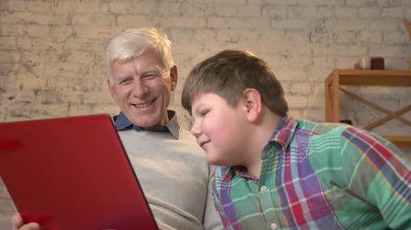 nicely : Grandfather and grandson are sitting on the couch and watching a funny movie on the laptop, laughing, speaking. Home comfort, family idyll, cosiness concept, difference of generations. Close up 60 fps