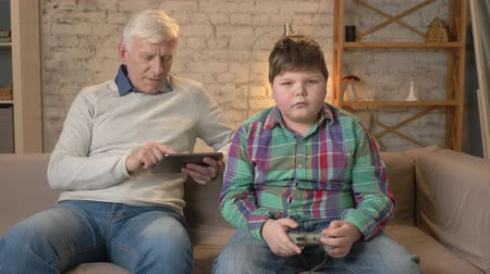 nicely : Grandfather and grandson are sitting on the couch. An old man uses a tablet, a young fat guy plays on the console game. Video games. Home comfort, family idyll, cosiness concept, difference of generations. 60 fps