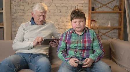 разница : Grandfather and grandson are sitting on the couch. An old man uses a tablet, a young fat guy plays on the console game. Video games. Home comfort, family idyll, cosiness concept, difference of generations 60 fps Стоковые видеозаписи