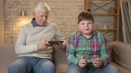 nicely : Grandfather and grandson are sitting on the couch. An old man uses a tablet, a young fat guy plays on the console game, loses. Video games. Home comfort, family idyll, cosiness concept, difference of generations 60 fps Stock Footage