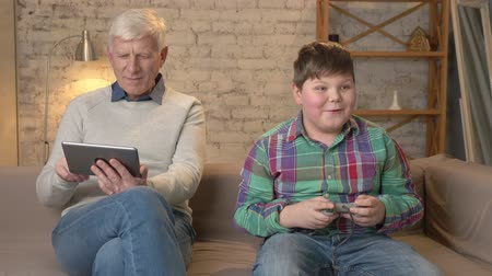 cosiness : Grandfather and grandson are sitting on the couch. An old man uses a tablet, a young fat guy plays on the console game, passionate. Video games. Home comfort, family idyll, cosiness concept, difference of generations. 60 fps Stock Footage