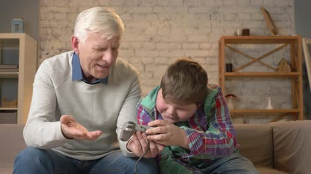 nicely : The grandson teaches grandfather to play the console game. Elderly man is learning how to play a video game, he does not understand. Home comfort, family idyll, cosiness concept, difference of generations 60 fps
