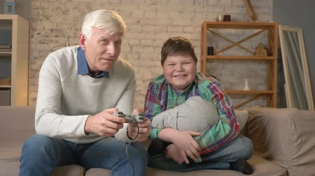 nicely : Grandpa plays in the console video game sitting on the couch with his grandson. An elderly man sits on the couch and holds game controller playing video games. Home comfort, family idyll, cosiness concept, difference of generations 60 fps