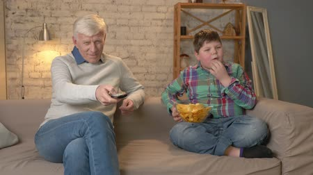 nicely : Grandfather and his grandson are sitting on the couch and watching television, eating chips. An elderly man switches channels, uses a remote control. Home comfort, family idyll, cosiness concept, difference of generations 60 fps