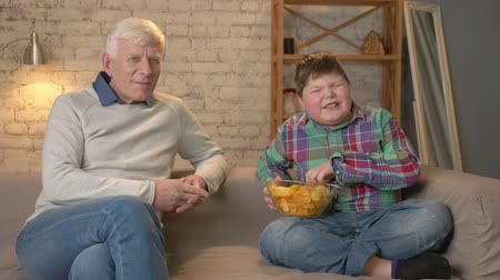 nicely : Grandfather and his grandson are sitting on the couch and watching television, eating chips, smiling. An elderly man switches channels, uses a remote control. Home comfort, family idyll, cosiness concept, difference of generations. 60 fps Stock Footage