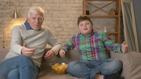 nicely : Grandfather and grandson are sitting on the couch watching television, eating chips, rejoicing in victory, fans. Home comfort, family idyll, cosiness concept, difference of generations. 60 fps