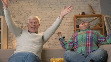 nicely : Grandfather and grandson are sitting on the couch and watching TV, eating chips, enjoying victory, fans, happy, smiling. Home comfort, family idyll, cosiness concept, difference of generations. 60 fps Stock Footage