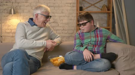 nicely : Grandfather is feeding his grandson with chips from his hands. An elderly man and a young fat boy are sitting on the couch in 3d glasses. Home comfort, family idyll, cosiness concept, difference of generations. 60 fps