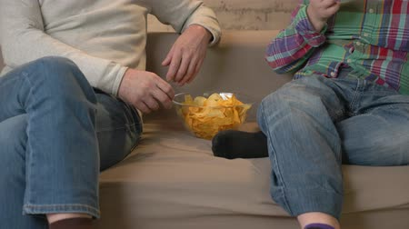 nicely : Grandfather and grandson are sitting on the couch and watching TV, eating chips. Home comfort, family idyll, cosiness concept, difference of generations 60 fps