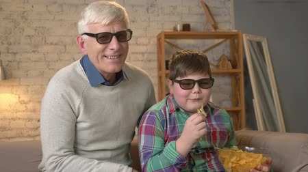 nicely : Grandfather and grandson are sitting on the couch and watching a 3D movie in 3d glasses, eating chips, laughing, smiling, comedy, humor, TV, show. Home comfort, family idyll, cosiness concept, difference of generations 60 fps