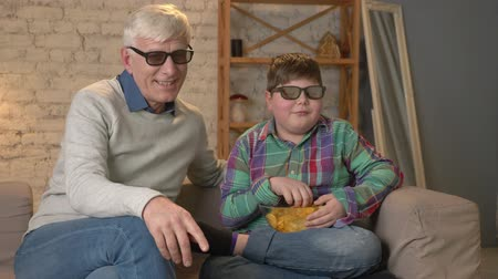 nicely : Grandfather and grandson are sitting on the couch and watching a 3D movie in 3d glasses, eating chips, TV, show. Home comfort, family idyll, cosiness concept, difference of generations. 60 fps