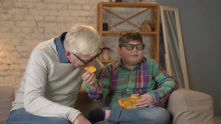 nicely : Grandson feeds his grandfather with chips from his hand. Grandfather and grandson are sitting on the couch and watching a 3D movie in 3d glasses, eating chips, TV, show. Home comfort, family idyll, cosiness concept, difference of generations. 60 fps