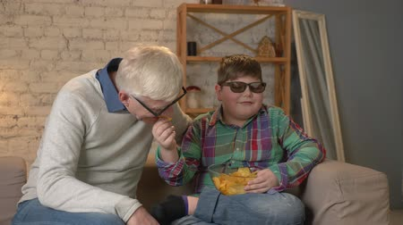 nicely : Grandson feeds his grandfather with chips from his hand. Grandfather and grandson are sitting on the couch and watching a 3D movie in 3d glasses, eating chips, TV, show. Home comfort, family idyll, cosiness concept, difference of generations 60 fps