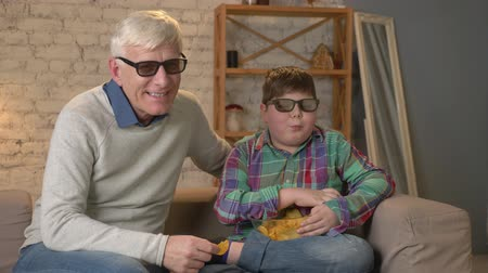 madde : Grandfather and grandson are sitting on the couch and watching a 3D movie in 3d glasses, eating chips, smiling, TV, show. Home comfort, family idyll, cosiness concept, difference of generations 60 fps
