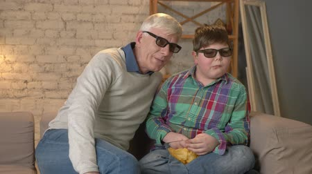 watch tv : Grandfather and grandson are sitting on the couch and watching a 3D movie in 3d glasses, eating chips, moving, TV, show. Home comfort, family idyll, cosiness concept, difference of generations 60 fps Stock Footage