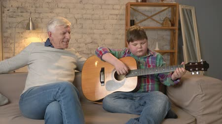 cosiness : The grandson plays for his grandfather guitar, music. An elderly man is sitting on with a young fat guy playing guitar. Home comfort, family idyll, cosiness concept, difference of generations 60 fps