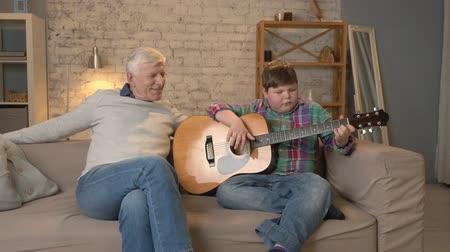 nicely : The grandson plays for his grandfather guitar, music. An elderly man is sitting on with a young fat guy playing guitar. Home comfort, family idyll, cosiness concept, difference of generations. 60 fps