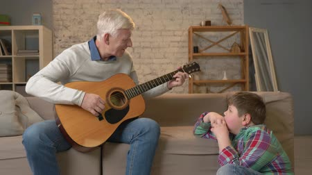 cosiness : Grandpa plays for his grandson on guitar, music. A young fat guy is sitting on the haven with his grandfather. Teaches his grandson playing the guitar. Home comfort, family idyll, cosiness concept, difference of generations 60 fps Stock Footage