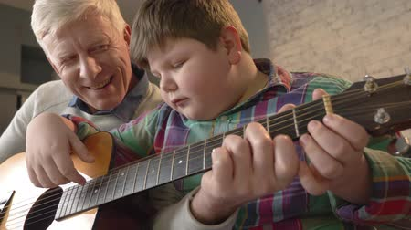 nicely : Grandfather is teaching his grandson how to play the guitar. An elderly man is teaching a young fat child to play guitar. Home comfort, family idyll, cosiness concept, difference of generations 60 fps