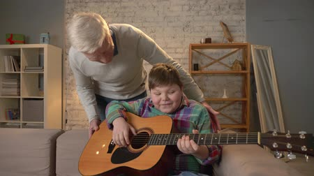 nicely : Grandpa gives his grandson a guitar, a gift, a surprise. An elderly man gives a guitar to a young fat child. Home comfort, family idyll, cosiness concept, difference of generations, close up 60 fps