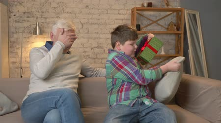 teen age : Grandson gives his Grandfather a gift. a fat child gives a gift to An elderly man, Joy, surprise, happiness, emotion, feeling, impulsively, present. Home comfort, family idyll, cosiness concept, difference of generations, close up. 60 fps