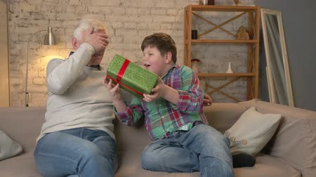 cosiness : Grandson gives his Grandfather a gift. a fat child gives a gift to An elderly man, Joy, surprise, happiness, emotion, feeling, impulsively, present, hug. Home comfort, family idyll, cosiness concept, difference of generations, close up. 60 fps