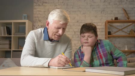 dede : Grandpa helps a grandson with homework. Elderly man helps a young fat child to do homework. Home comfort, family idyll, cosiness concept, difference of generations, close up. 60 fps Stok Video