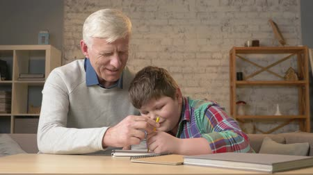 teen age : Grandpa helps a grandson with homework. Elderly man helps a young fat child to do homework. Home comfort, family idyll, cosiness concept, difference of generations, close up. 60 fps Stock Footage