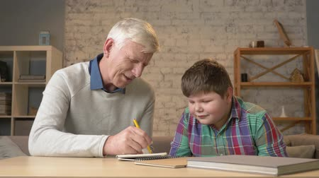 nicely : Grandpa helps a grandson with homework. Elderly man helps a young fat child to do homework. Home comfort, family idyll, cosiness concept, difference of generations, close up. 60 fps Stock Footage