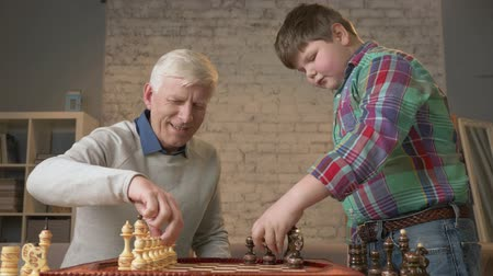 harc : Grandfather and grandson are preparing to play chess. An elderly man teaches a fat child how to play chess. Expose the pieces on the chessboard. Home comfort, family idyll, cosiness concept, difference of generations, close up. 60 fps Stock mozgókép