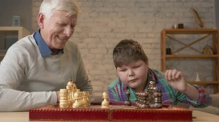 sudden : Grandfather and grandson plays chess. Elderly man teaches chess to play a young fat child. Home comfort, family idyll, cosiness concept, difference of generations, close up. 60 fps
