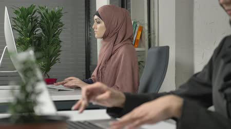 культ : Female hands typing on the keyboard, close-up. Girl in pink hijab in the background. Office, business, work, women, concept. Arabs, Islam, hijab, religion, 60 fps