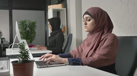 культ : Two Muslim girls in hijabs work in the office, type on the keyboard, look at the monitor and look at the camera at the end. Office, business, work, women, concept. 60 fps Стоковые видеозаписи