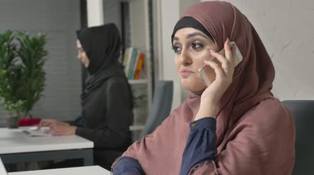 culto : Young beautiful girl in pink hijab sits in the office and speaks on the smartphone, laughing. 60 fps